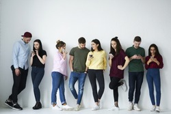 Full length portrait of group of diverse people use smartphones against copy space background with area for your advertising. Young friends in casual wear holding cellphones  using popular application