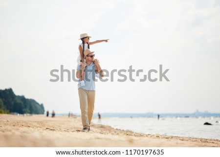 5b2c1a33a4 Full length portrait of handsome modern dad carrying curious little girl on  his shoulders enjoying walk