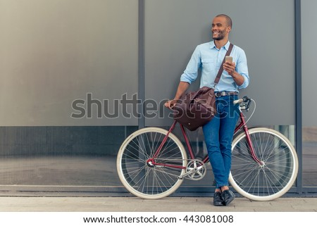 Full length portrait of handsome young Afro American man in casual clothes using phone, looking away and smiling while leaning on his bike, standing outdoors