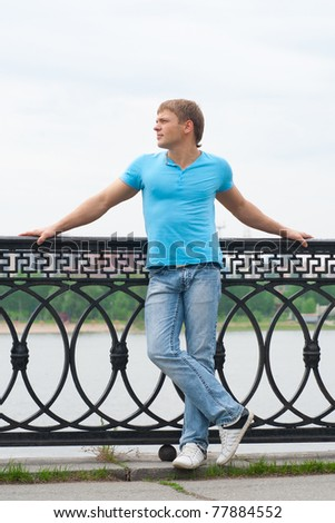 Full length portrait of handsome young man standing outdoors