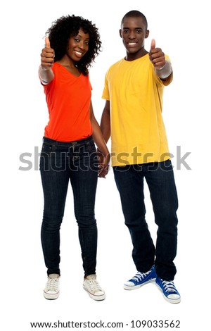 Full length portrait of happy african couple showing thumbs up