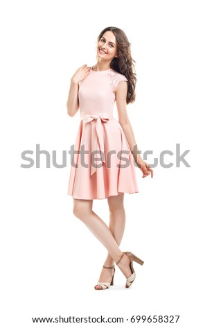 Full length portrait of happy beautiful woman in pink dress posing in studio isolated on white background