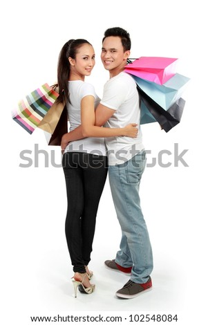 full length portrait of happy couple carrying shopping bag on white background