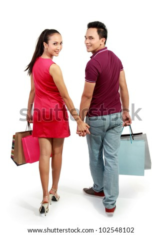 full length portrait of happy couple walking with shopping bag on white background
