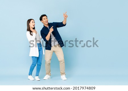 Full length portrait of happy excited Asian couple tourists pointing hands to empty space on isolated light blue background
