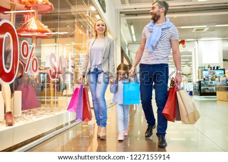 c75ec1192b Full length portrait of happy family shopping in mall walking past window  displays with sale signs