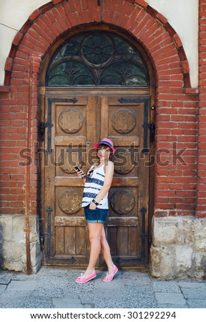 Full length portrait of happy girl smiling, with mobile phone wearing stylish pink hat and striped shirt and denim shorts. On the background of old wooden doors with a pattern.
