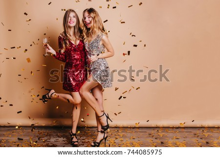 Full-length portrait of happy girls wears high heel shoes dancing at party under confetti. Indoor photo of funny ladies chilling at home during christmas celebration and drinking champagne. #744085975