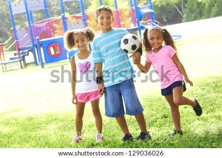 Full length portrait of happy little children with soccer ball at park. Horizontal shot.