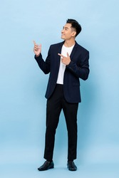 Full length portrait of happy smiling young handsome southeast Asian businessman pointing and looking upward on light blue studio background