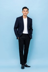Full length portrait of happy smiling young handsome southeast Asian businessman standing on light blue studio background