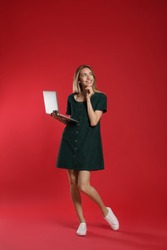 Full length portrait of happy woman with modern laptop on red background