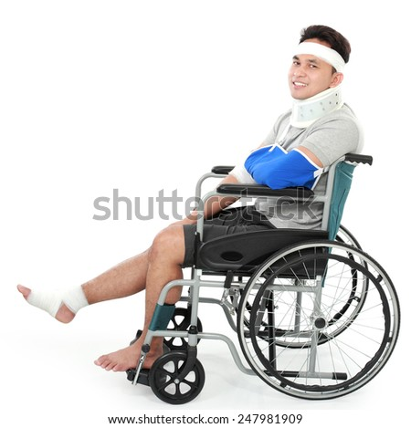 full length portrait of injured young man in wheelchair facing the copy space