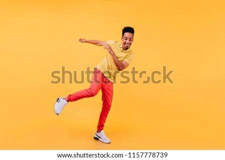 Full-length portrait of joyful african male model dancing in yellow shoes. Cheerful black man enjoying photoshoot on bright background.