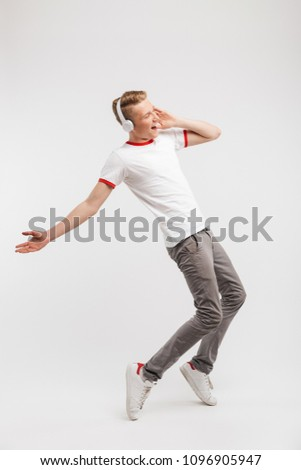 Full length portrait of joyous boy wearing casual clothing dancing and singing while listening to music via headphones isolated over white background