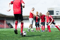 Full length portrait of junior football team practice, back view unrecognizable boy leading ball, copy space