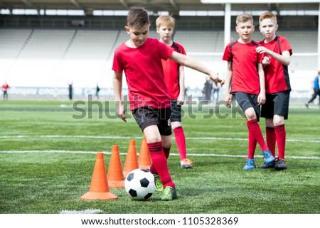 Full length portrait of junior football team practicing in stadium, focus on teenage boy leading ball between  row of orange cones, copy space #1105328369