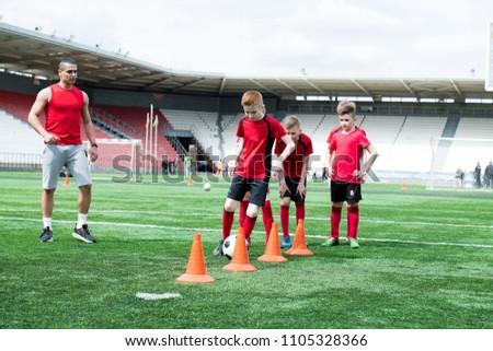 Full length portrait of junior football team practicing in stadium, row of boys leading ball between orange cones, copy space #1105328366