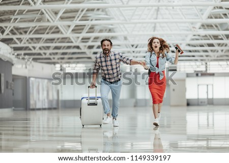 Full length portrait of laughing bearded man with suitcase and outgoing girl with documents and phone in hand hurrying at airport