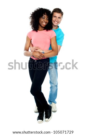 Full length portrait of love couple embracing against white background. Indoor shot