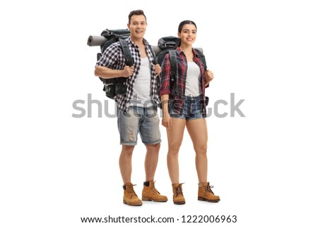 Full length portrait of male and female hikers with backpacks standing and looking at the camera isolated on white background