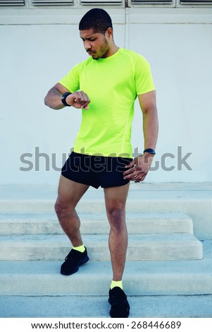 Full length portrait of male runner looking at his watch while going for a run at sunny afternoon,sporty young man dressed in bright t-shirt with space for your text message checking his time outdoors stock photo