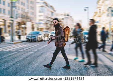 Full length portrait of male tourist with backpack from designer crossing across road and looking at camera during weekend in Russia, hipster guy in sunglasses walking and enjoying trip to Moscow