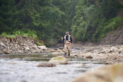 Full length portrait of man walking in river with two professional rods. Competent fisherman enjoying fishing during leisure time on fresh air.