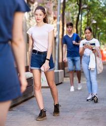 Full length portrait of modern teen girl dressed in white tee shirt and jorts walking along city street on summer day