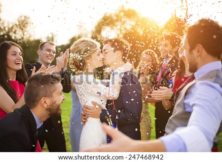 Full length portrait of newlywed couple and their friends at the wedding party showered with confetti in green sunny park #247468942