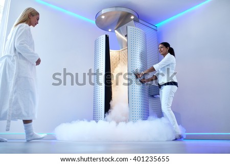 Full length portrait of nurse opening the door of cryosauna, with woman in bathrobe at the clinic. Female going for cryotherapy treatment in freezing cabinet.