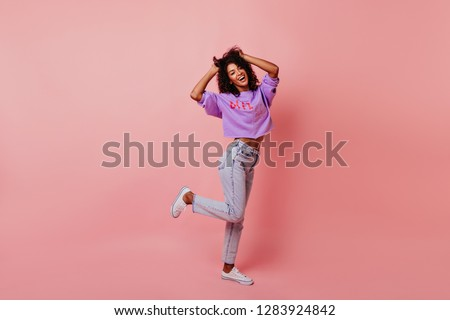 Full-length portrait of optimistic laughing woman dancing in studio. Relaxed curly female model enjoying life.
