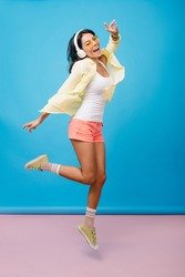 Full-length portrait of pleased girl in white tank-top and yellow shoes jumping on blue background. Enchanting brunette asian woman in headphones funny dancing and singing.