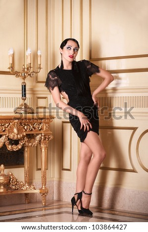 Full-length portrait of posing retro-style woman in black dress in luxury interior