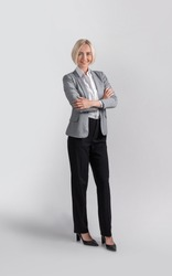 Full length portrait of positive female entrepreneur in formal clothes over light grey studio background. Beautiful businesswoman standing with crossed arms and smiling