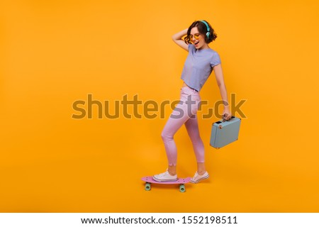 Full-length portrait of positive girl with blue valise posing on orange background. Jocund curly female model standing on longboard and smiling.