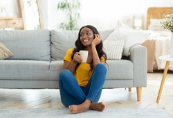 Full length portrait of pretty black lady sitting on floor with cup of hot drink, indoors. Lovely African American woman having coffee break from hectic day, chilling at home on weekend