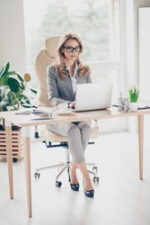 Full length portrait of pretty, charming, blonde woman using, browsing, typing, searching, working online on computer, sitting at desktop  in workstation, using wifi internet