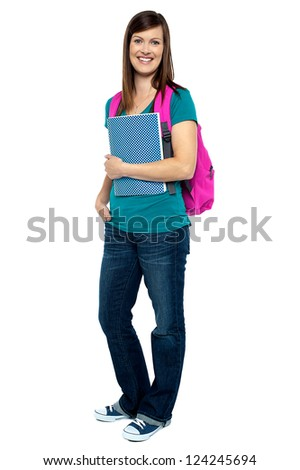 Full length portrait of pretty college girl carrying pink backpack. Casual studio shot.