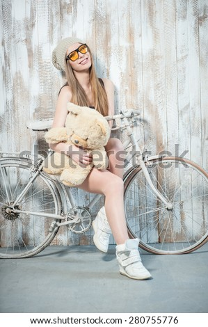 Full length portrait of pretty hipster girl with teddy bear, whom she is hugging while smiling and sitting on the bicycle. She is wearing cool sunglasses and looking at the camera.
