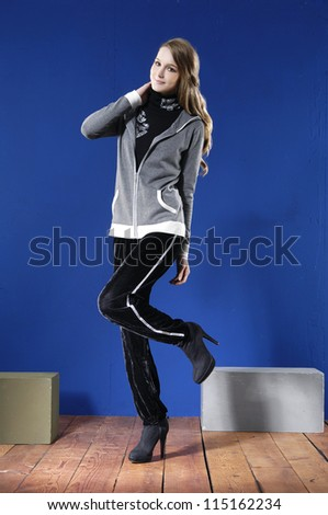 Full length portrait of pretty young woman posing with cube