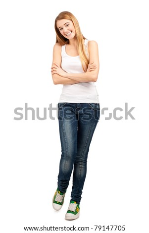 Full length portrait of pretty young woman standing with folded hands and smiling, against white background