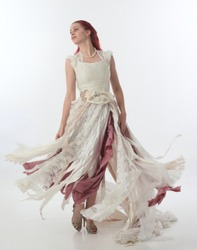 full length portrait of red haired girl wearing torn and tattered wedding dress. Standing pose against a  white studio background.