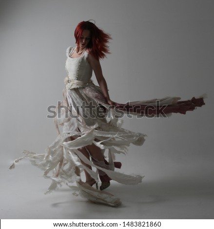 full length portrait of red haired girl wearing torn and tattered wedding dress. Standing pose against a studio background with contrasty shadow lighting. #1483821860
