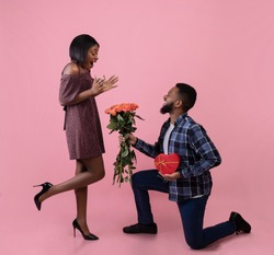 Full length portrait of romantic black guy giving his girlfriend flowers and gift for Valentine's Day over pink studio background. Excited woman receiving roses and present from her boyfriend
