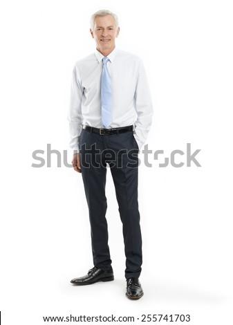 Full length portrait of senior businessman standing against white background.
