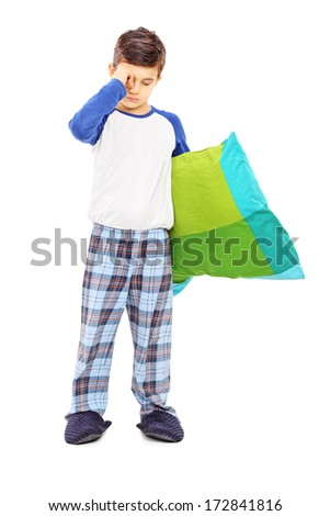 Full length portrait of sleepy kid holding a pillow isolated on white background