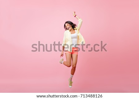 Full-length portrait of slim young woman with tanned skin jumping with smile on pink background. Studio portrait of happy brunette girl in yellow shirt, dancing and singing with eyes closed.
