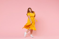Full length portrait of smiling beautiful charming young redhead plus size body positive female woman girl 20s in yellow dress posing looking camera isolated on pastel pink color background studio