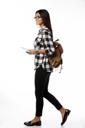 Full length portrait of smiling female student wearing glasses and  plaid shirt with tablet computer and backpack walking side. over white background
